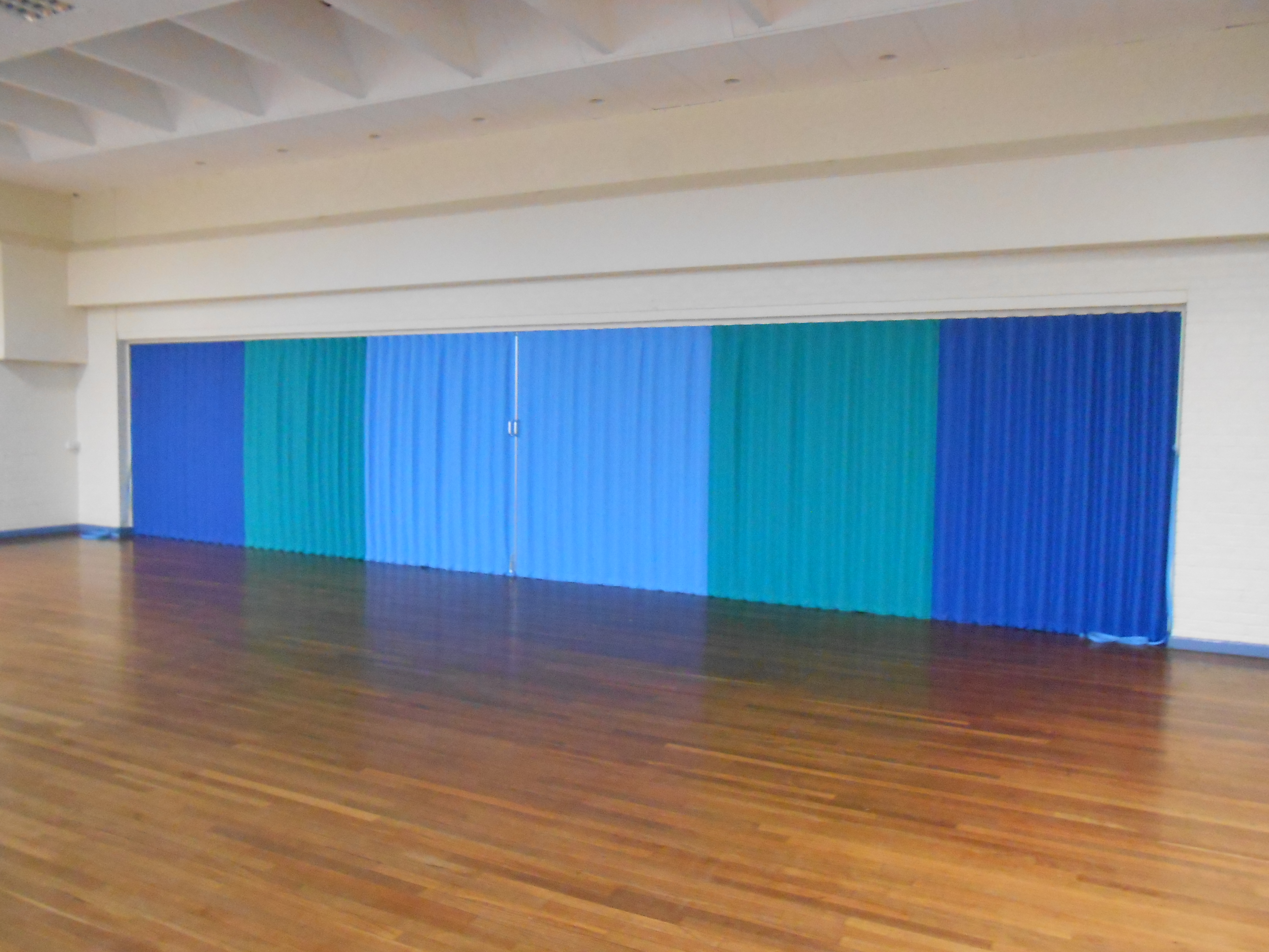blue concertina folding fabric partitions in a school hall