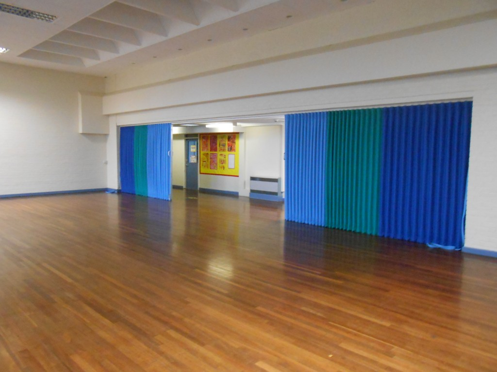 blue folding sliding room partitions in a school hall.