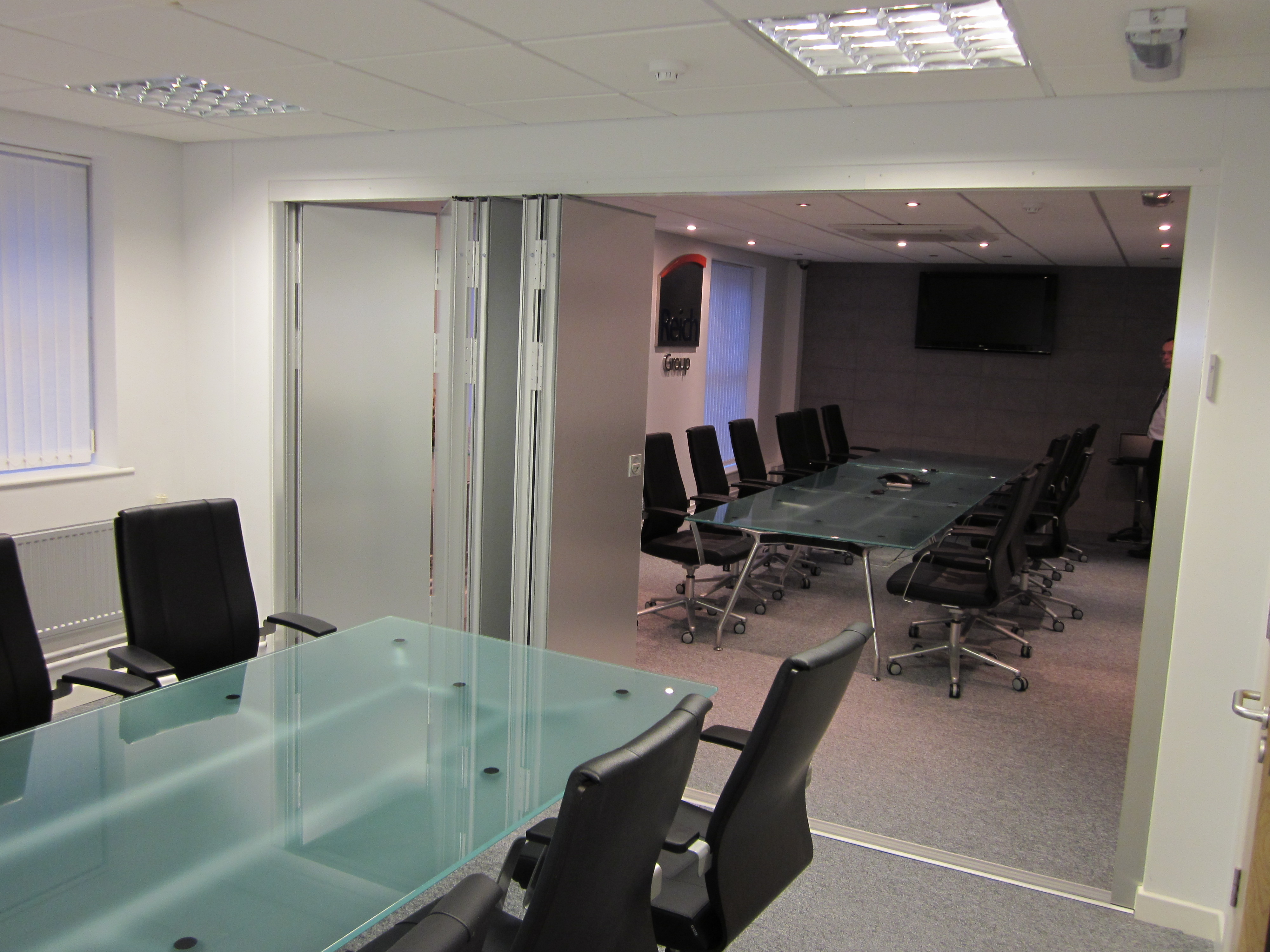 multifold folding partitions shown open between two office spaces with glass tables