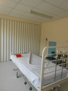 hospital bed with folding fabric room divider in white