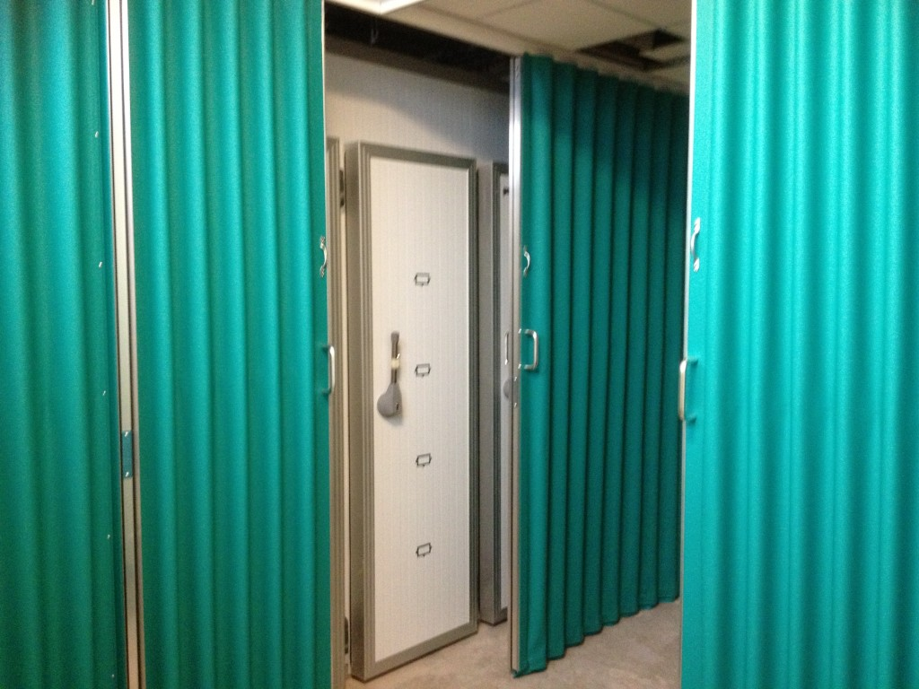 folding green fabric room divider in a hospital